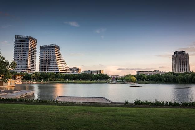 Edificio comercial moderno al atardecer junto al pequeño lago Foto Premium