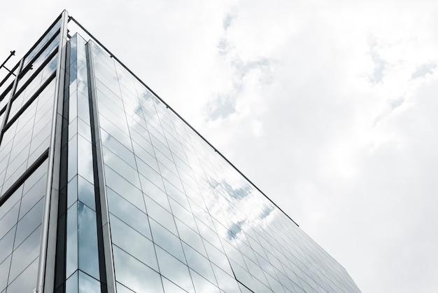 Edificio de cristal de ángulo bajo con nubes Foto gratis