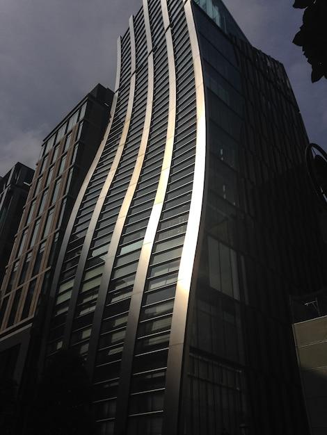 Edificio con curvas bañado por la luz solar directa en tokio Foto Premium