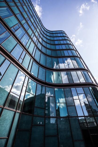 Un edificio de gran altura en una fachada de vidrio con el reflejo de los edificios circundantes. Foto gratis