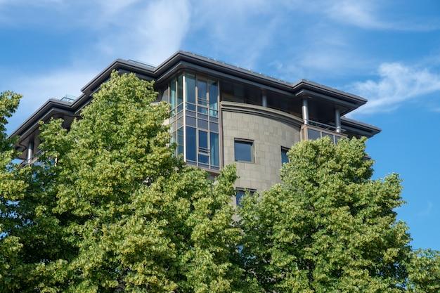 Edificio moderno detrás de árboles verdes contra un primer azul cielo nublado en un día soleado de verano Foto Premium