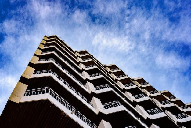Edificio residencial de patrones arquitectónicos simétricos con fondo de nubes azules Foto Premium