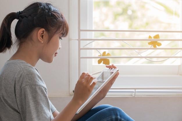 Educación, aprendizaje, estudio en línea joven asiática hermosa estudiante uso tableta para buscar Foto Premium