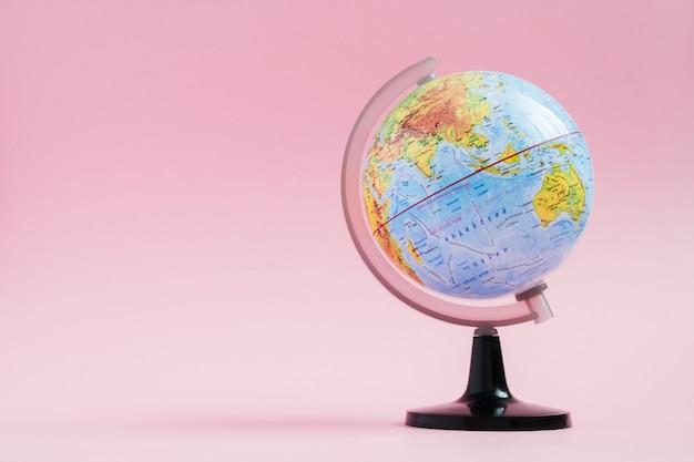 Educación de historias de aventuras con globo terráqueo sobre fondo rosa Foto Premium
