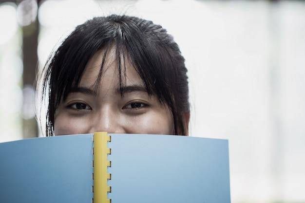 Educación para el libro de lectura y el concepto de estudio de aprendizaje: estudiante asiático mirando a la cámara Foto Premium