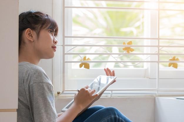 Educación que aprende el concepto en línea del estudio: smartphone hermoso del uso que se sienta del estudiante hermoso asiático joven Foto Premium