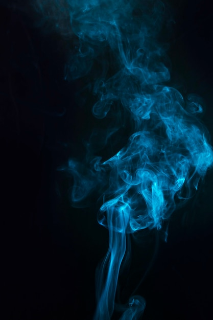 Efecto humo de color azul sobre fondo negro. Foto gratis