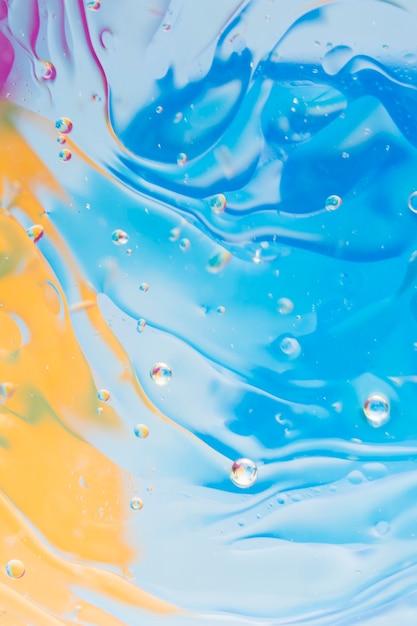 Efecto líquido sobre el fondo pintado azul y amarillo Foto gratis