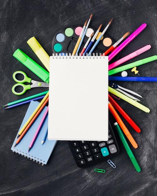 Efectos de escritorio coloridos, pinturas, calculadora debajo del cuaderno en fondo gris Foto gratis