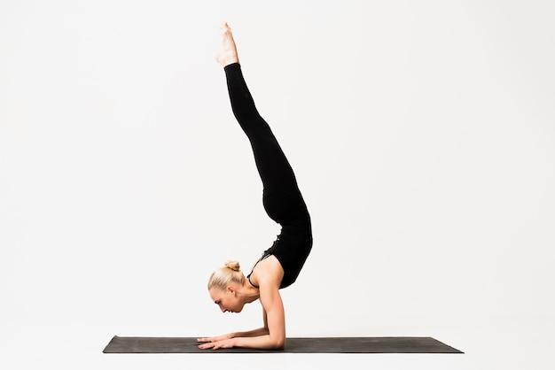Ejecución de posición de vela clase de yoga interior Foto gratis
