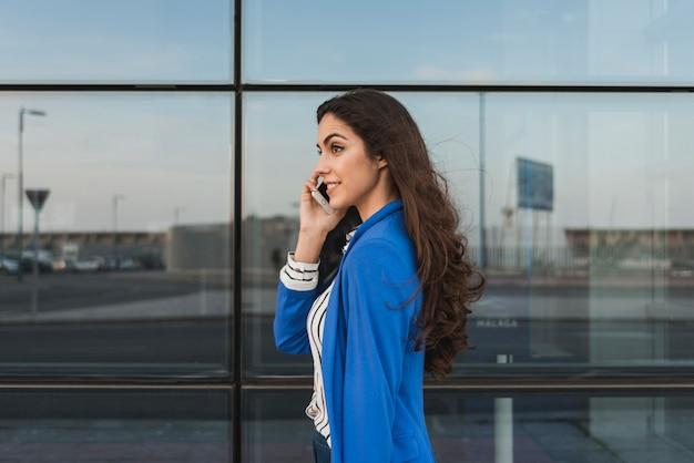 Ejecutiva joven hablando por teléfono con edificio de cristal de fondo Foto gratis