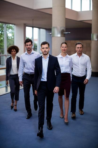 Ejecutivos de negocios caminando en el lobby de un centro de conferencias Foto gratis