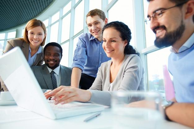 Ejecutivos sonrientes teniendo una reunión alrededor de la mesa Foto gratis