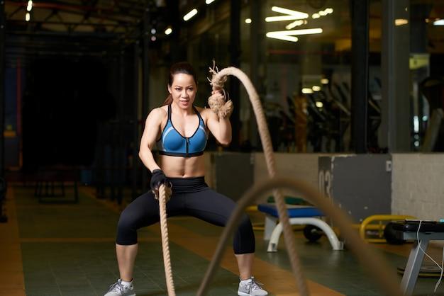 Ejercicio de crossfit realizado por una mujer fuerte con cuerda Foto gratis