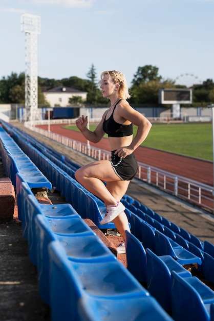 Ejercicio de escaleras de mujer joven en el estadio Foto gratis