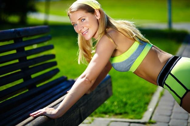 Ejercicio mujer haciendo flexiones en entrenamiento al aire libre entrenamiento deporte fitness mujer sonriendo alegre y feliz Foto gratis