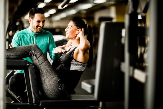 Ejercicio de mujer joven con la ayuda del entrenador en el gimnasio Foto Premium