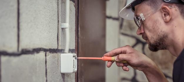 Electricista-técnico masculino, conecta el equipo con una herramienta Foto gratis
