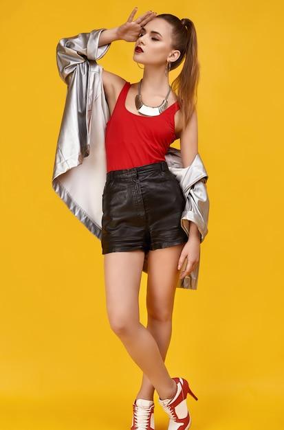 Elegante chica glamour hipster en top rojo, shorts negros y chaqueta vaquera Foto Premium