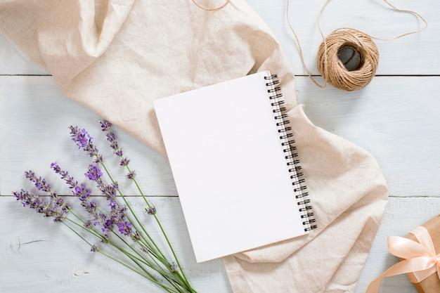 Elegante composición con flores de lavanda, bloc de notas de papel en blanco, manta de color beige pastel, cordel, caja de regalo en una rústica mesa de escritorio de madera azul Foto Premium