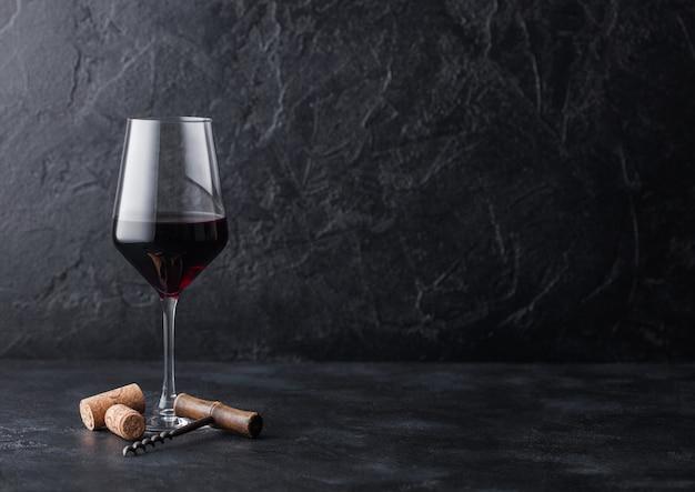 Elegante copa de vino tinto con corchos y sacacorchos sobre fondo de piedra negra. Foto Premium