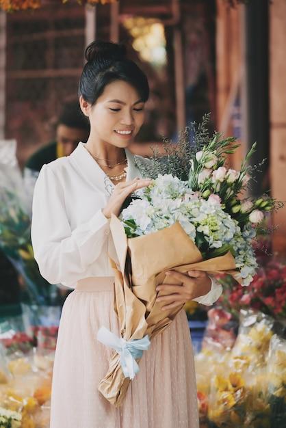 Elegante dama asiática admirando el elaborado ramo de flores frescas en la floristería Foto gratis