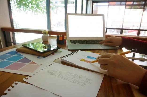 993a17fda Elegante diseñador de moda de trabajo como boceto de la nueva colección en  el taller.