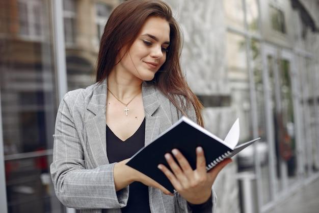 Elegante empresaria que trabaja en una ciudad y usa el cuaderno Foto gratis