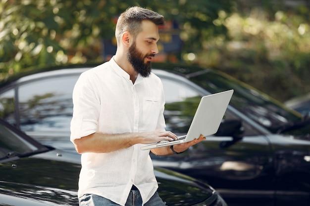 Elegante empresario de pie cerca del coche y usar la computadora portátil Foto gratis