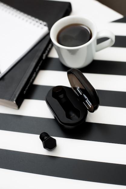 Elegante espacio de trabajo minimalista con maqueta portátil, lápiz, taza de café, auricular inalámbrico Foto Premium