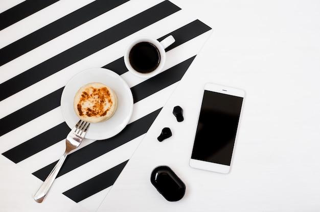 Elegante espacio de trabajo minimalista con maqueta de smartphone, libro, cuaderno, lápiz, taza de café Foto Premium