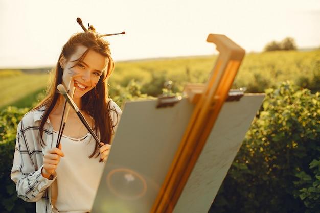 Elegante y hermosa niña pintando en un campo Foto gratis