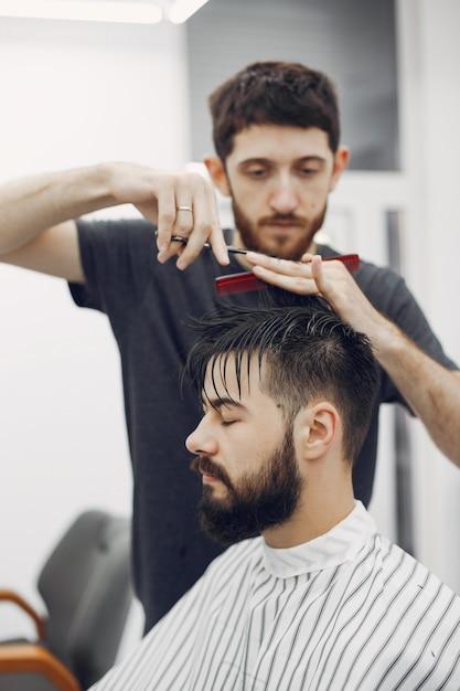 Elegante hombre sentado en una barbería Foto gratis