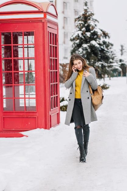 Elegante imagen británica de moda joven caminando en la calle en invierno cerca de la cabina de teléfono roja. hablar por teléfono, verdaderas emociones positivas, reír, sonreír. Foto gratis