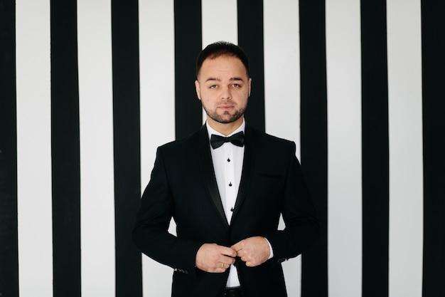 Elegante joven guapo en traje negro clásico. retrato de estudio de moda. Foto gratis