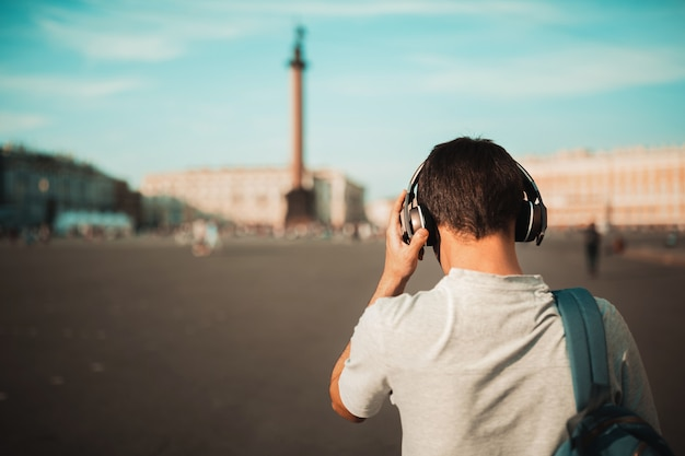 Elegante joven con mochila y auriculares inalámbricos al aire libre Foto Premium