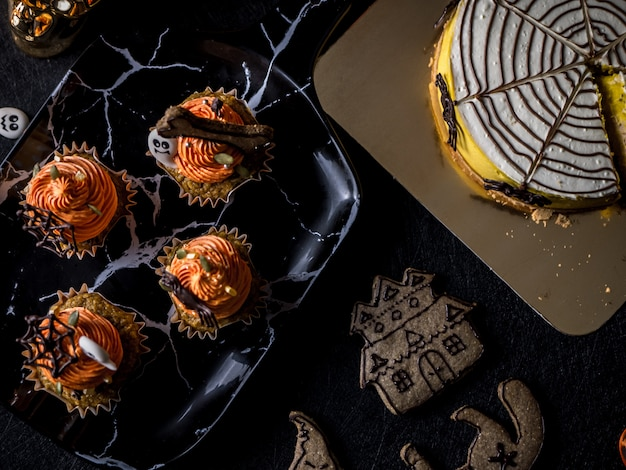 Elegante mesa de fiesta de comida de halloween con magdalena de calabaza y galletas. Foto Premium