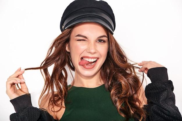 Elegante modelo de risa en ropa casual negra de verano en gorra con maquillaje natural en blanco, tocando el cabello y mostrando su lengua Foto gratis