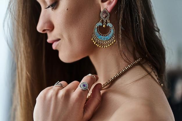 Elegante mujer boho chic sensual con grandes aretes, collar de oro y anillos de plata con piedra. traje bohemio gitano hippie indio de moda con accesorios de detalles de joyería Foto Premium
