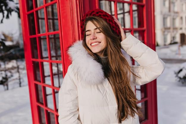 Elegante mujer de cabello castaño posando con sonrisa romántica y ojos cerrados durante el invierno en inglaterra. retrato al aire libre de mujer sonriente soñadora en boina de lana roja disfrutando de sesión de fotos cerca de la caja de llamada. Foto gratis