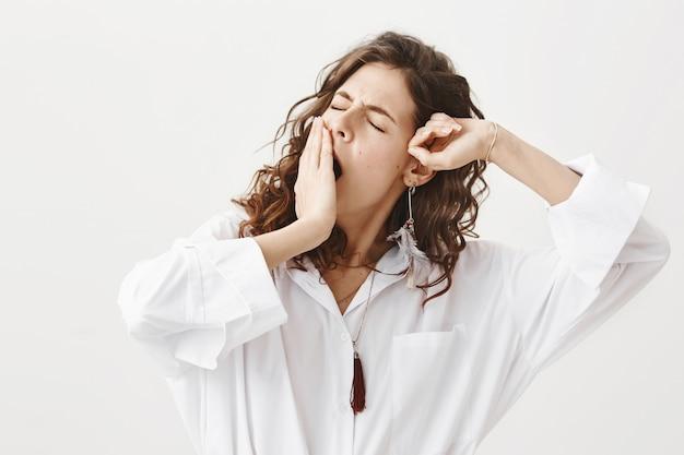 Elegante mujer dormida despertar, bostezar y estirar Foto gratis