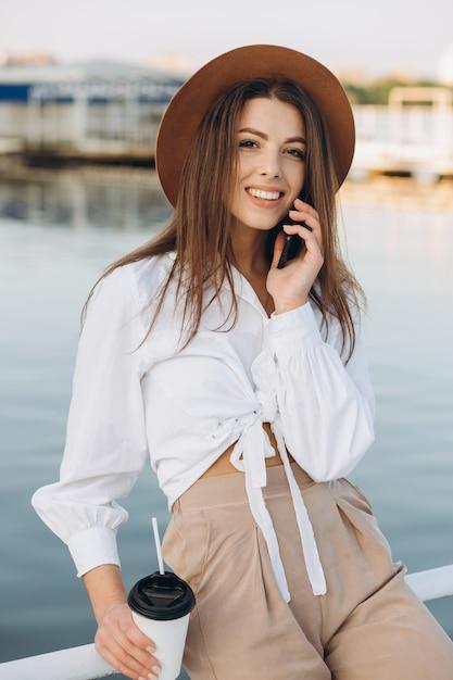 Una elegante mujer hablando por teléfono y caminando por la playa en un cálido día de verano al atardecer Foto Premium