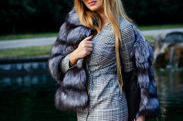 Elegante mujer joven en abrigo de pieles y vestido corto posando al aire libre. Foto Premium