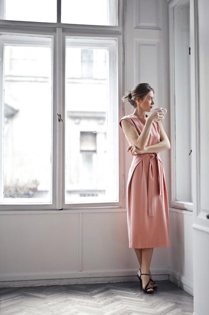 Elegante mujer mirando por la ventana Foto Premium