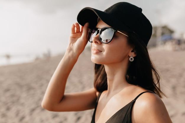 Elegante mujer moderna en traje de tendencia mirando al océano con una sonrisa feliz con gorra y gafas y disfruta de los días calurosos de verano modelo femenino caucásico joven en la orilla del mar Foto gratis
