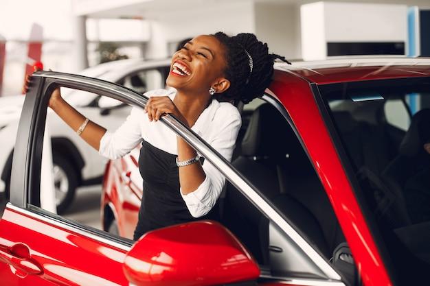 Elegante mujer negra en un salón de autos. Foto gratis