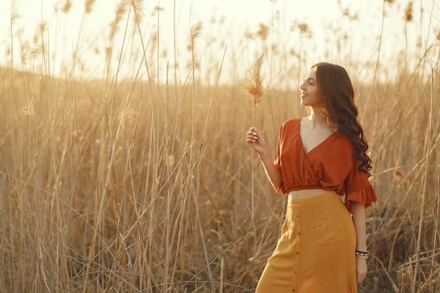 Elegante mujer pasar tiempo en un campo de verano Foto gratis
