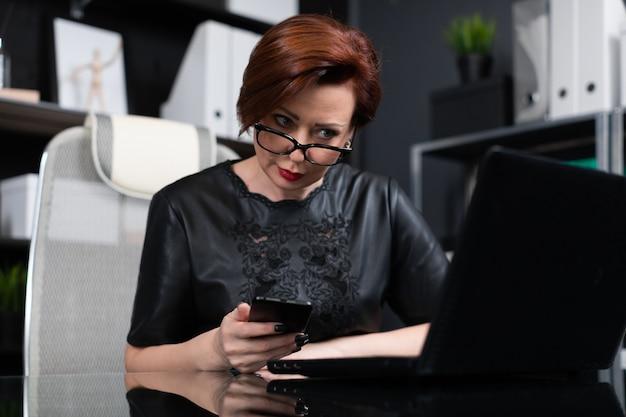 Elegante mujer que trabaja con ordenador portátil y teléfono en la oficina Foto Premium