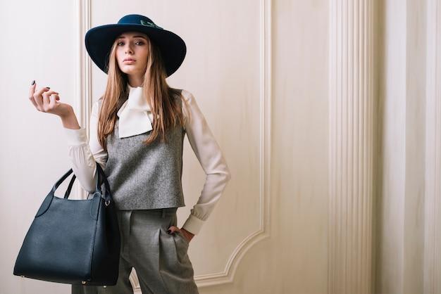Elegante mujer en traje y sombrero con bolso en habitación. Foto gratis