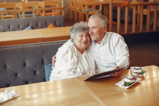 Elegante pareja de ancianos en un café con una tableta Foto gratis